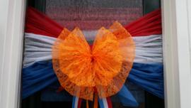 Oranje strik in kant met rood, wit, blauwe banden van papierachtig materiaal