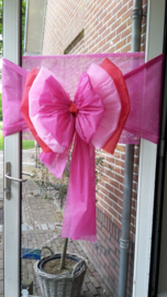 Deurstrik in drie kleuren: licht roze, fuchsia en rood