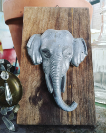 Old tin elephant on wooden plate