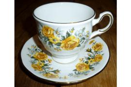 Kop en schotel met gele rozen