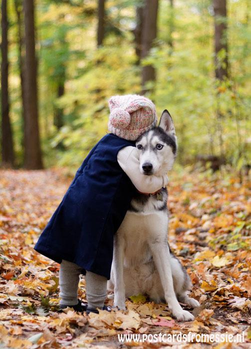 Child embraces dog