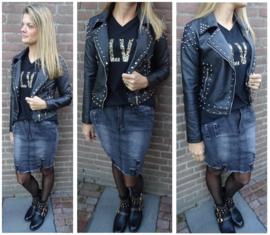 Zwart bikerjasje met studs in combinatie met statement shirt en grijze damesrok met damaged pekken