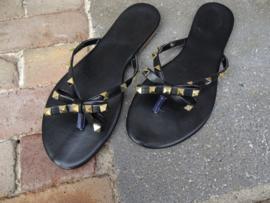 Zwarte slippers met studs in de vorm van een strik
