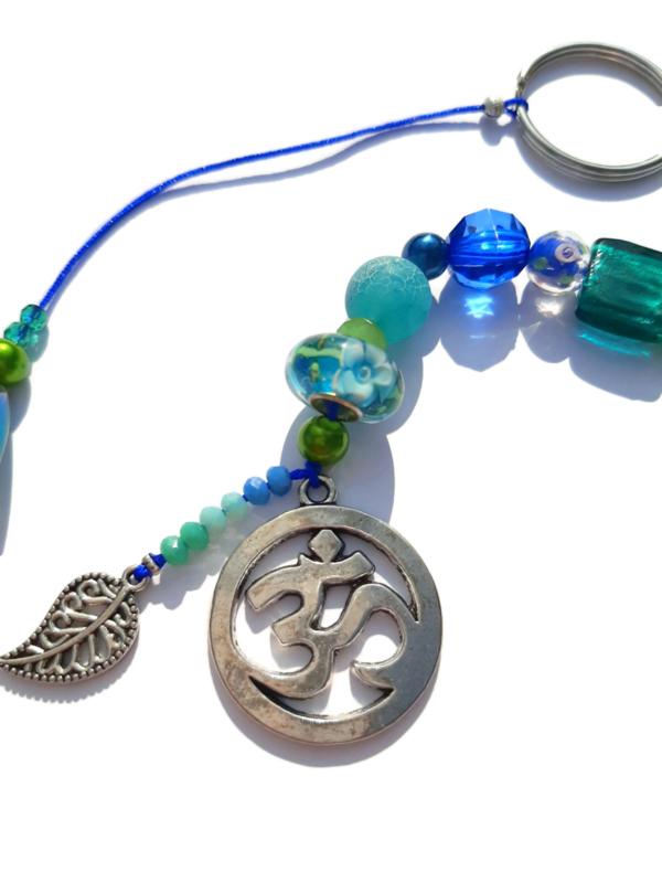 Ohm gelukshanger met blauwe en groene kralen