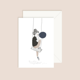Girl seated on swing inflating a blue balloon