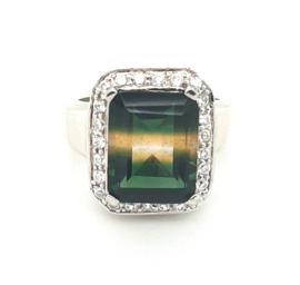 Occasion zilveren ring rijkelijk bezet met zirkonia's en een groen gele steen