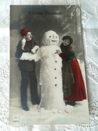 Ansichtkaart stel bij sneeuwpop kerst
