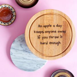 Snijplank met grappige tekst  AN APPLE A DAY KEEPS ANYONE AWAY IF YOU THROW IT HARD ENOUGH - Beukenhouten snijplank met een diameter van 25 cm