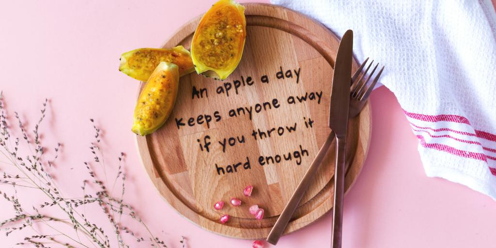 sfeerfoto-van-de-snijplank-met-de-tekst-an-apple-a-day-keeps-anyone-away-if-you-throw-it-hard-enough-van-gekkiggeit