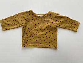 Tricot/stretch shirtje mosterd geel met roze/zwarte stipjes.