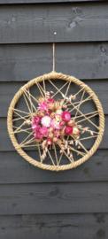 Roze droogbloemen op jute krans