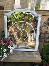 Verweerde spiegel met klok