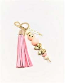 Roze gelukspoppetje - goudkleurige strikje