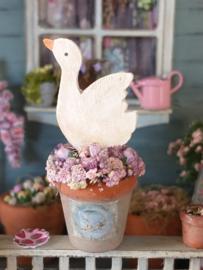 Bloempot met lila roosjes en een houten gans