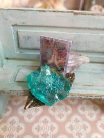 Bronskleurig blad met turquoise steen, prentje en een Amethist edel steen.