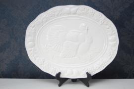 Groot wit porseleinen schaal met kalkoen in reliëf