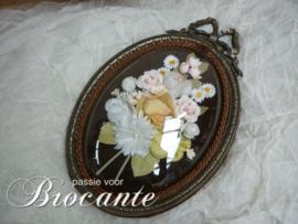Vintage kader met strik en bloemen onder gebombeerd glas