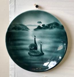 Wandbordje - Petrus Regout - décor 5022 in donker groen spuitdecor van twee zwanen in een meer met achteraan riet en bossages
