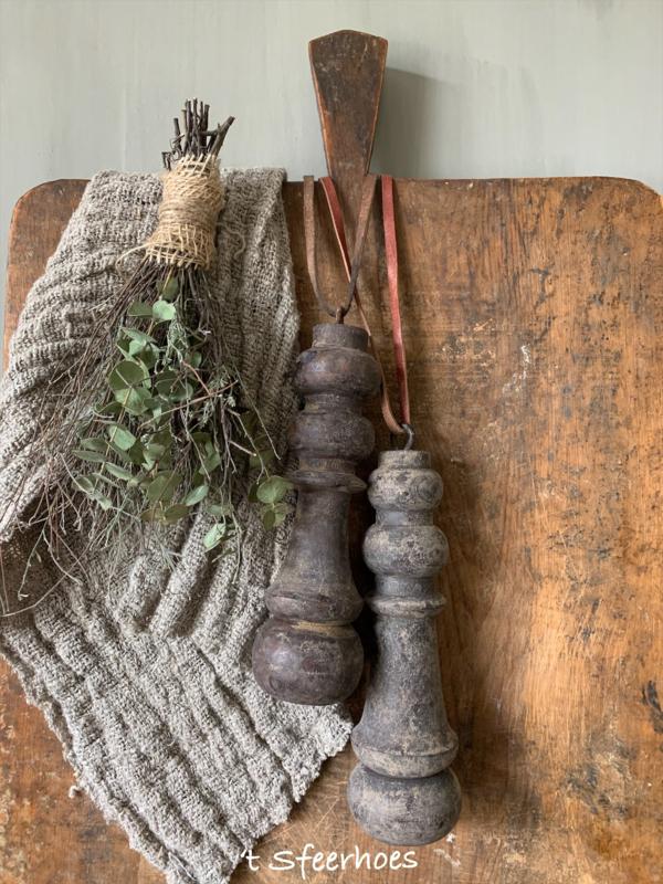 oude vergrijsde houten klos aan leren veter