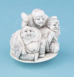 Netsuke of three figures.