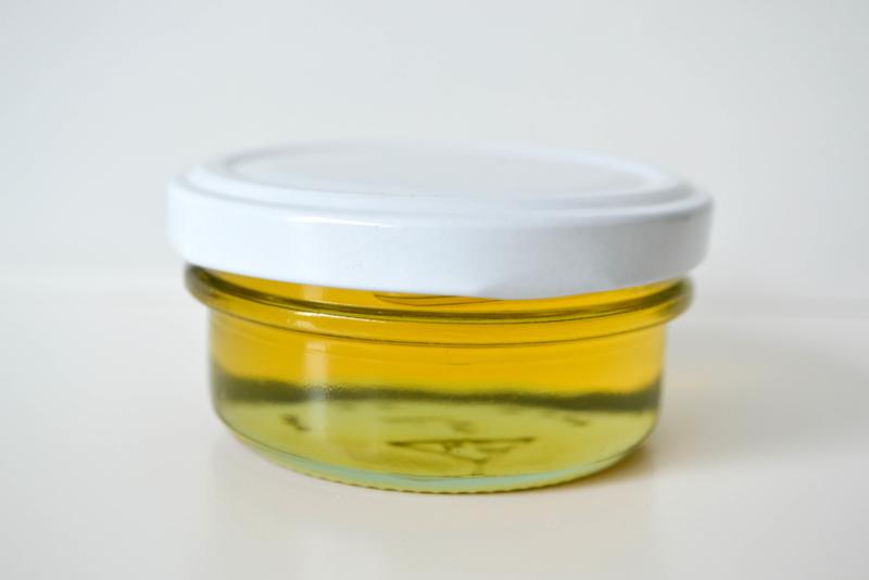 Glazen potje wit gevuld met 100% natuurlijke honing
