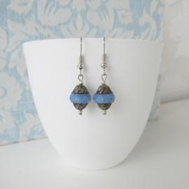 Zilverkleurige oorbellen met licht blauwe kraal.