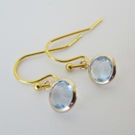 Goudkleurige  oorbellen met licht blauwe bedel