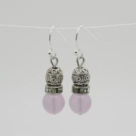 Zilverkleurige fantasie oorbellen met roze glazen kraal.