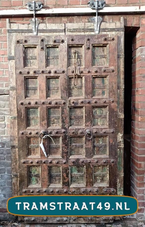 Oude deur als schuifdeur geplaatst aan railsysteem met hangrollen model 1920 van Tramstraat 49.