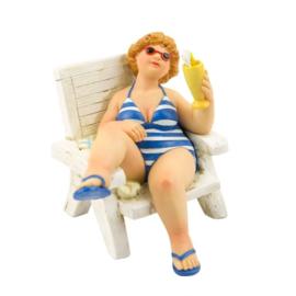 Dikke dame op strandstoel met een cocktail