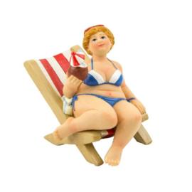 Dikke dame op strandstoel met een kokosnoot