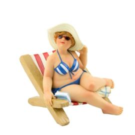 Dikke dame op strandstoel met hoed op