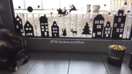 Huisjes met sterren, kerstboom, lantaarnpalen, maan, kerstpop en kerstman met slee