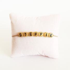Armbandje beige elastiek + gouden kraal met zwarte letter