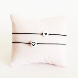 Vriendschapsarmbandjes 2x zwart elastiek + witte kraal met zwart hartje