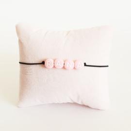 Armbandje zwart elastiek + roze kraal met witte letter
