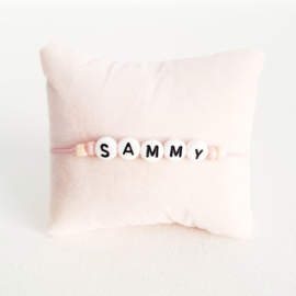 Armbandje roze elastiek + witte kraal met zwarte letter + licht roze en rosé gouden rocaille