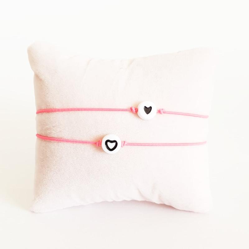 Vriendschapsarmbandjes 2x fluor roze elastiek + witte kraal met zwart hartje