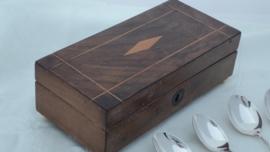 Verzilverde theelepeltjes in houten opbergdoosje.