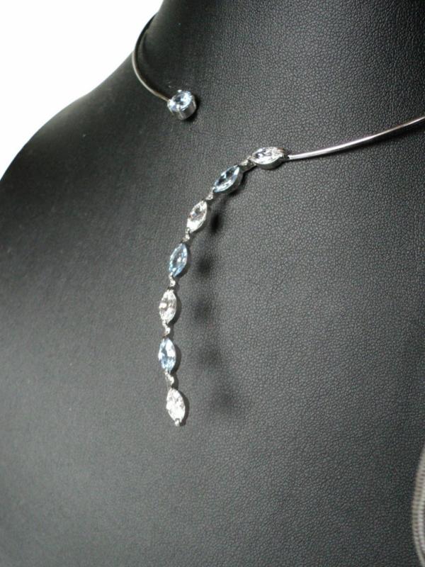 Zilveren spang met witte  en l.blauwe zirconia's.